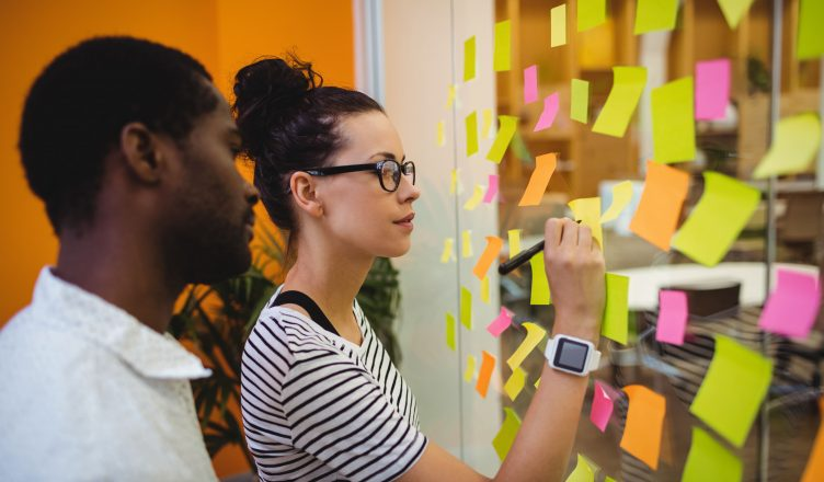 Business executives writing on sticky notes in office
